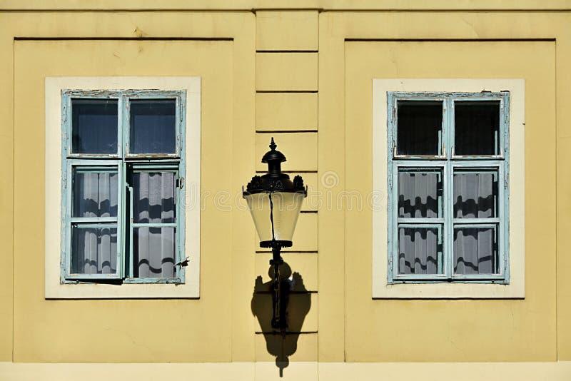 Due finestre sulla parete gialla con la lampada in mezzo immagine stock libera da diritti