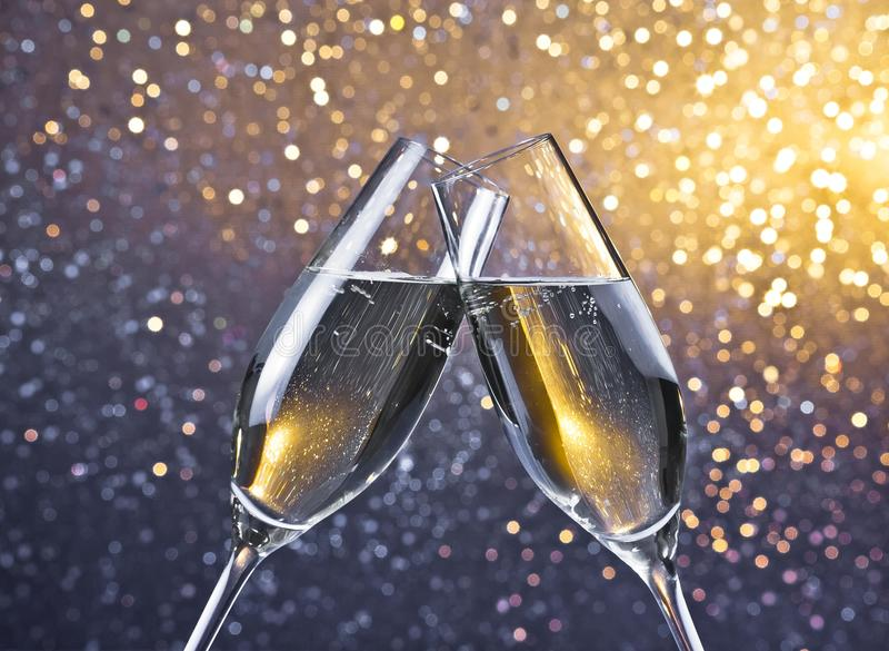 Due flûte con le bolle dorate sul fondo leggero del bokeh immagine stock