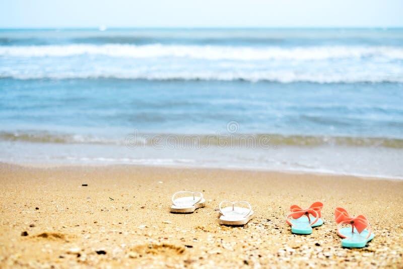 Due Flip-flop di paia sulla spiaggia fotografie stock