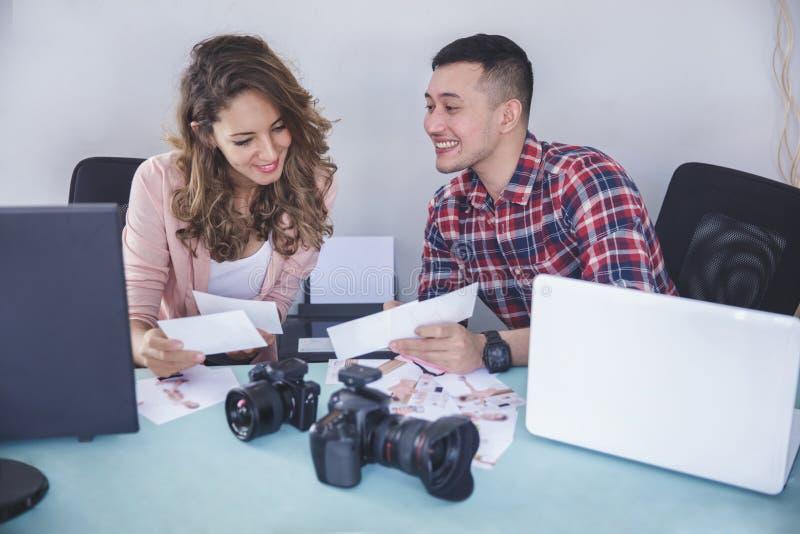 Due fotografi che esaminano la loro foto risultano dopo i sess della foto fotografie stock
