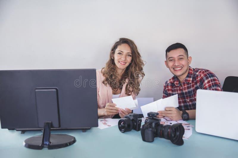 Due fotografi che sorridono e che esaminano macchina fotografica mentre tenendo Th immagine stock libera da diritti