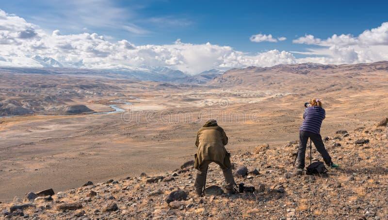 Due fotografi in montagne Un uomo dai capelli grigi in un rivestimento del cammuffamento e una ragazza dai capelli rossi in un ma immagine stock