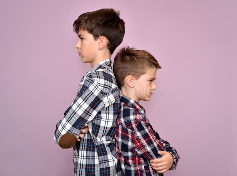 Due fratelli arrabbiati che stanno di nuovo alla parte posteriore fotografie stock libere da diritti
