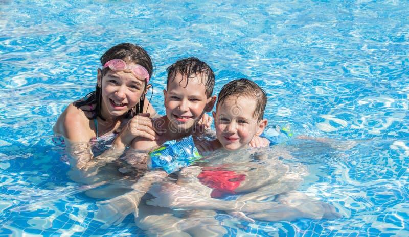 Due fratelli e pi? vecchia nuotata della sorella nello stagno dei bambini all'aperto felice fotografie stock