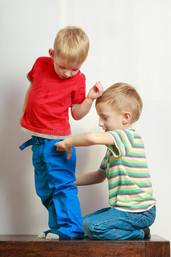 Due fratelli germani dei ragazzini che giocano insieme sulla tavola immagine stock