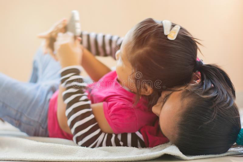 Due fratelli germani indiani svegli del litlle che combattono per il telefono cellulare, striscianti ad a vicenda sul letto fotografia stock