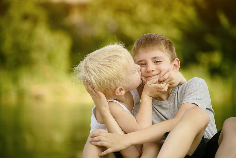 Due fratelli piccoli stanno sedendo all'aperto Si bacia l'altro sulla guancia Alberi verdi vaghi nella distanza Concetto di fotografie stock libere da diritti