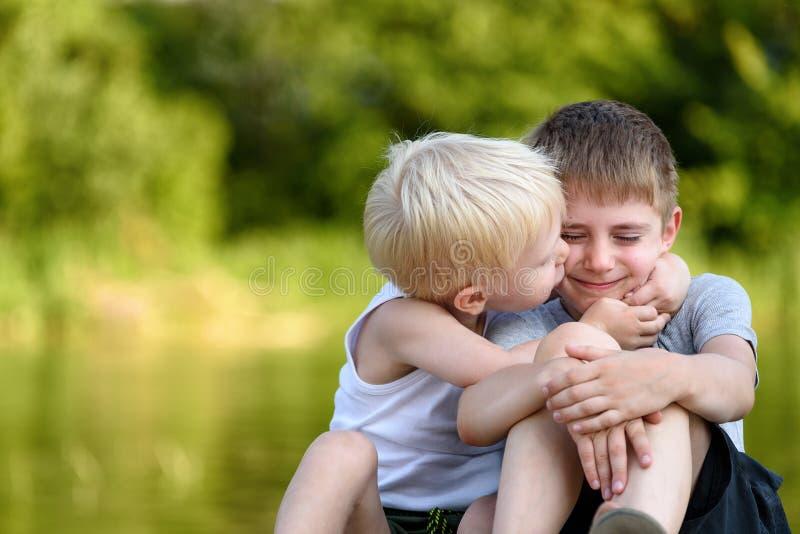 Due fratelli piccoli stanno sedendo all'aperto Si bacia l'altro sulla guancia Alberi verdi vaghi nella distanza Concetto di fotografie stock