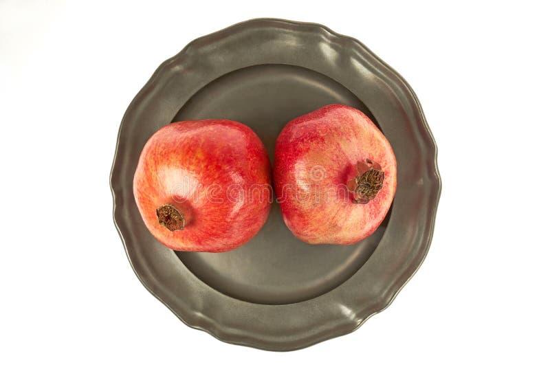 Due frutti maturi del melograno su un di piastra metallica, centrale da sopra sopra un fondo bianco immagine stock