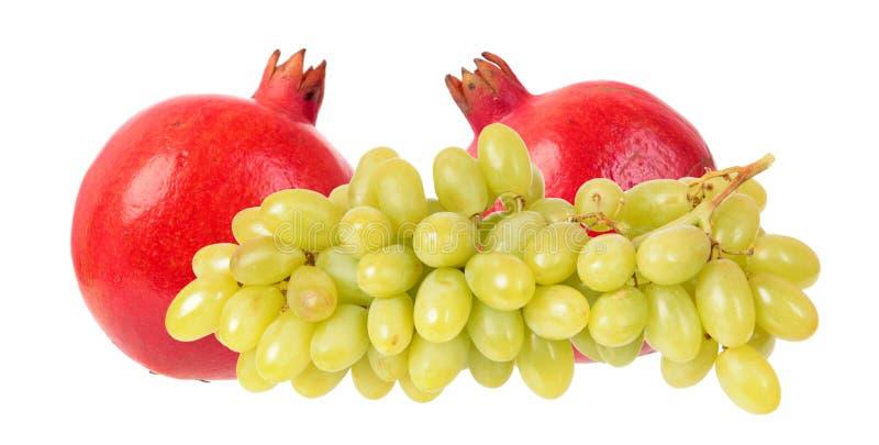 Due frutti rossi del melograno ed uva verde isolati su fondo bianco fotografia stock