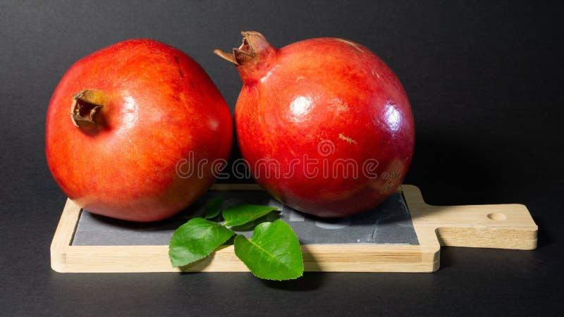 Due frutti succosi luminosi del melograno e del fogliame verde, fondo nero fotografie stock libere da diritti