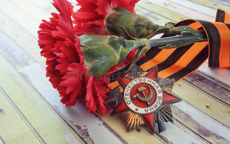 Due garofani con il nastro del ` s di StGeorge e un premio Patrioti fotografie stock