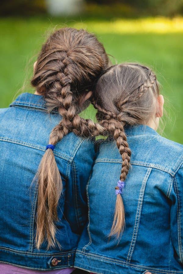Due gemelli con le trecce lunghe legate fotografia stock