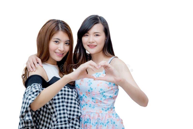 Due gemelli della donna che mostrano forma del cuore con le mani immagine stock