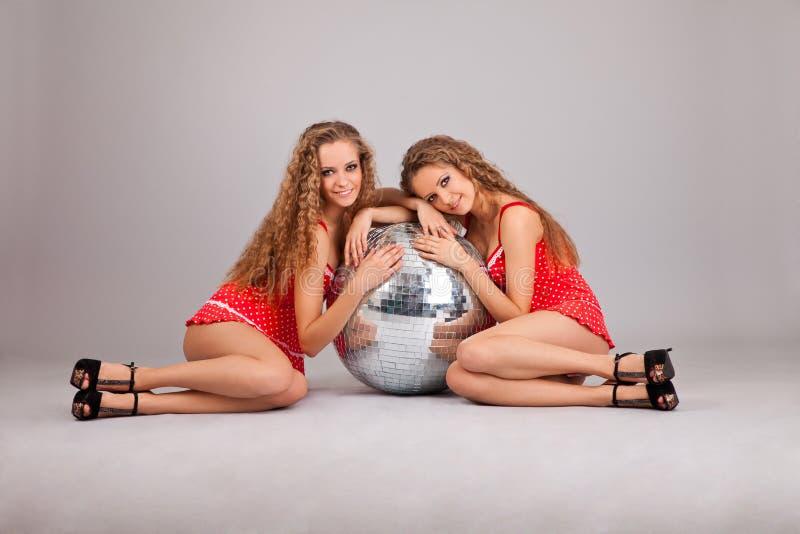 Due gemelli delle ragazze con glitterball su grey fotografia stock libera da diritti