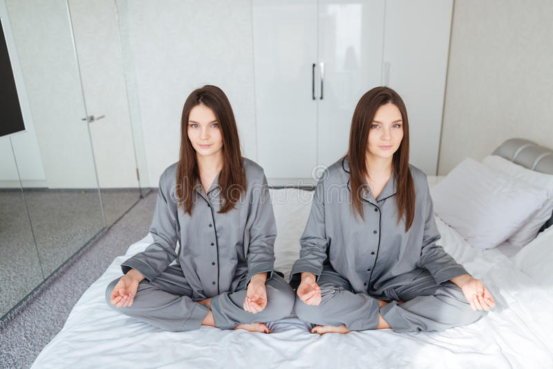 Due gemelli delle sorelle che praticano yoga e che meditano su letto fotografia stock libera da diritti
