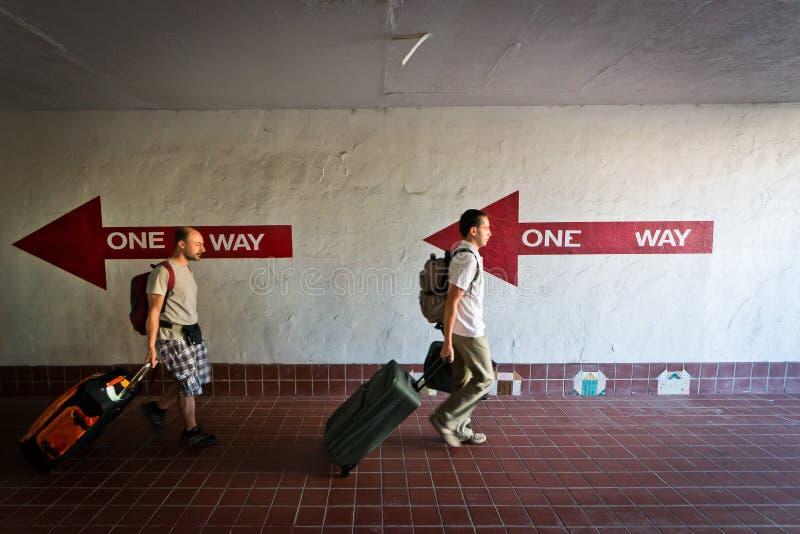 Due genti che camminano nella direzione sbagliata con sui immagine stock
