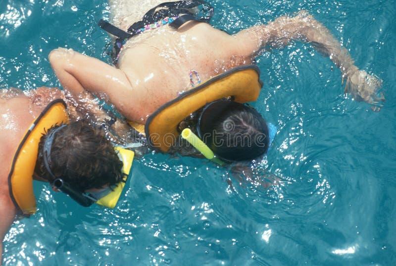 Due genti che navigano usando una presa d'aria in acqua immagini stock