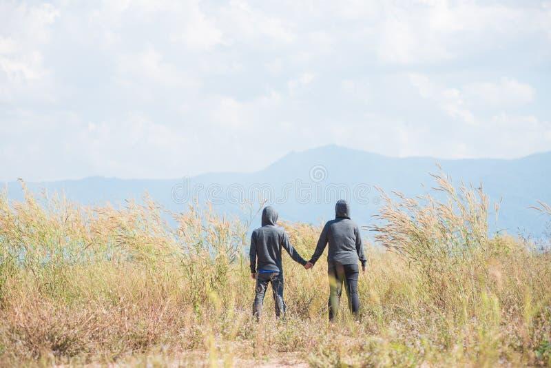 Due genti che stanno e che si tengono per mano fotografia stock