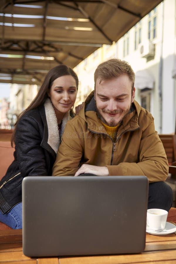 Due genti comuni, 20-29 anni, esaminanti computer portatile in un caffè immagine stock