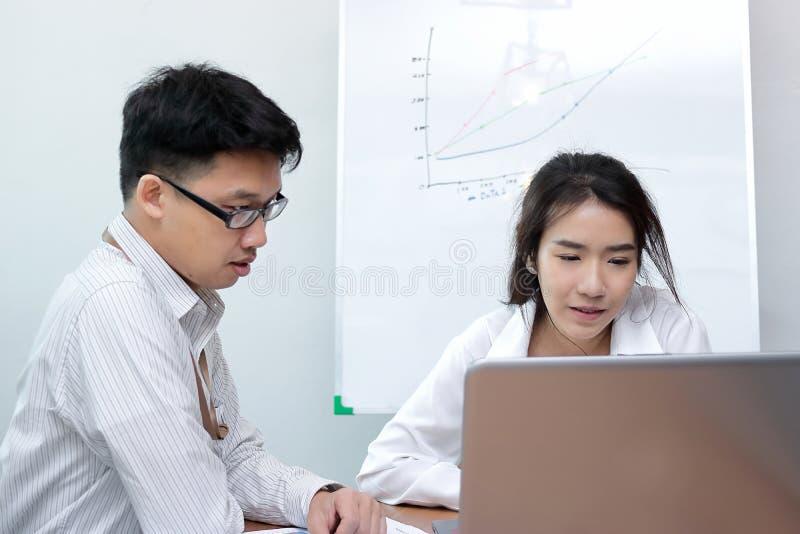Due genti di affari asiatiche che lavorano insieme su un computer portatile all'ufficio fotografia stock