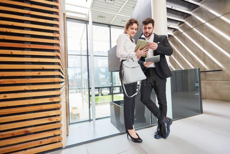 Due genti di affari con il computer della compressa in gruppo immagini stock