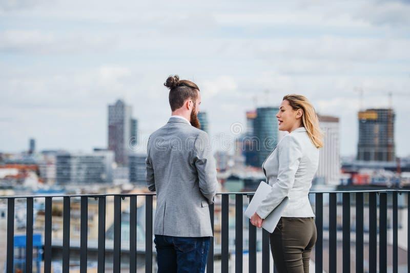 Due genti di affari con la compressa che sta su un terrazzo fuori dell'ufficio, parlante fotografia stock