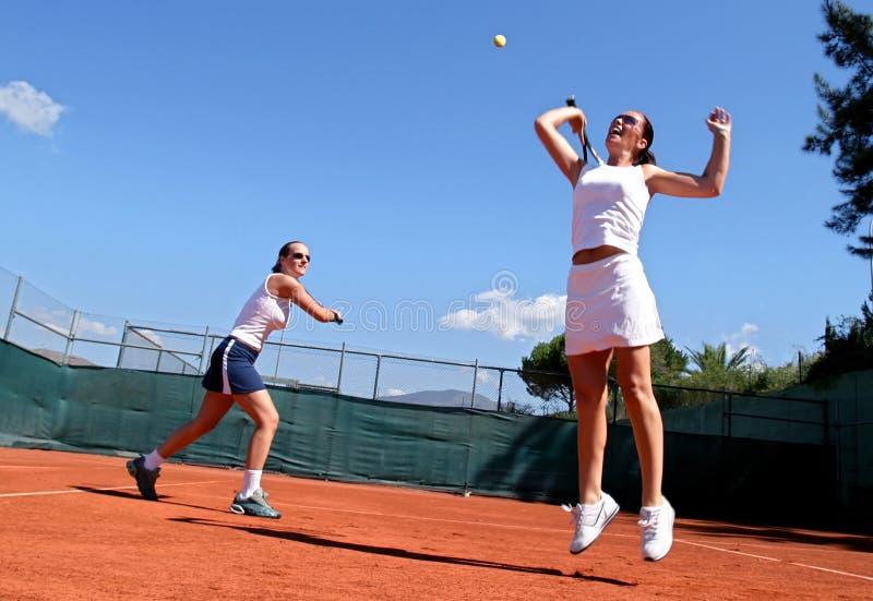Due giocatori di tennis femminili che giocano i doppi al sole. Uno è saltellante ed allungante per la sfera. fotografia stock libera da diritti