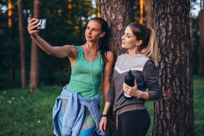 Due giovani amiche allegre che portano abiti sportivi che pendono contro l'albero che prende selfie con lo smartphone in foresta fotografie stock libere da diritti