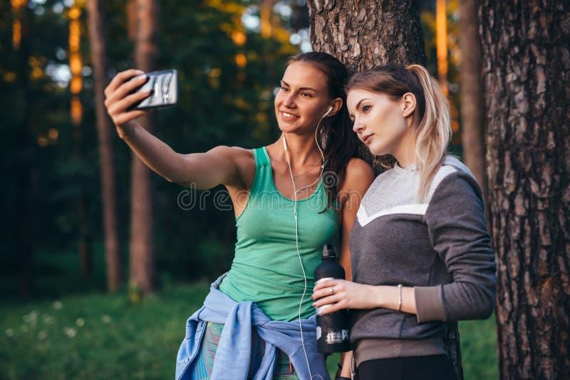 Due giovani amiche allegre che portano abiti sportivi che pendono contro l'albero che prende selfie con lo smartphone in foresta fotografia stock libera da diritti