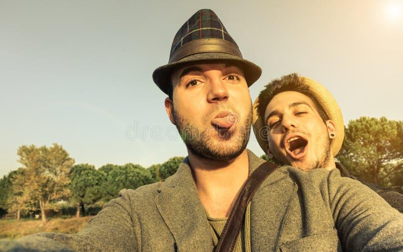 Due giovani amici dei pantaloni a vita bassa che prendono selfie all'aperto nelle feste - F fotografia stock