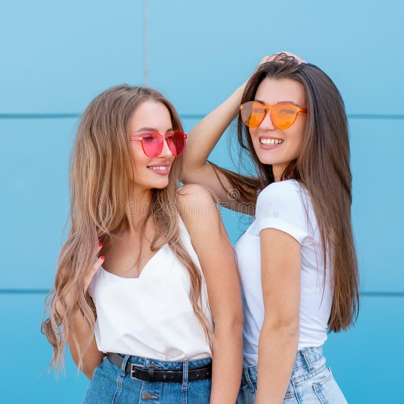 Due giovani amici della donna dei pantaloni a vita bassa in retro occhiali da sole al neon che stanno e che sorridono sopra la pa fotografia stock libera da diritti