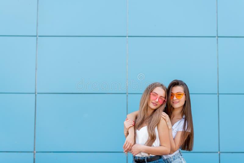 Due giovani amici della donna dei pantaloni a vita bassa in retro occhiali da sole al neon che stanno e che sorridono sopra la pa immagini stock libere da diritti