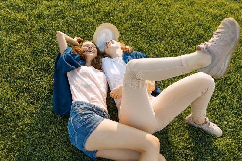 Due giovani amici di ragazze sorridenti si trovano abbracciando sull'erba verde nel parco soleggiato dell'estate, vista superiore fotografia stock libera da diritti