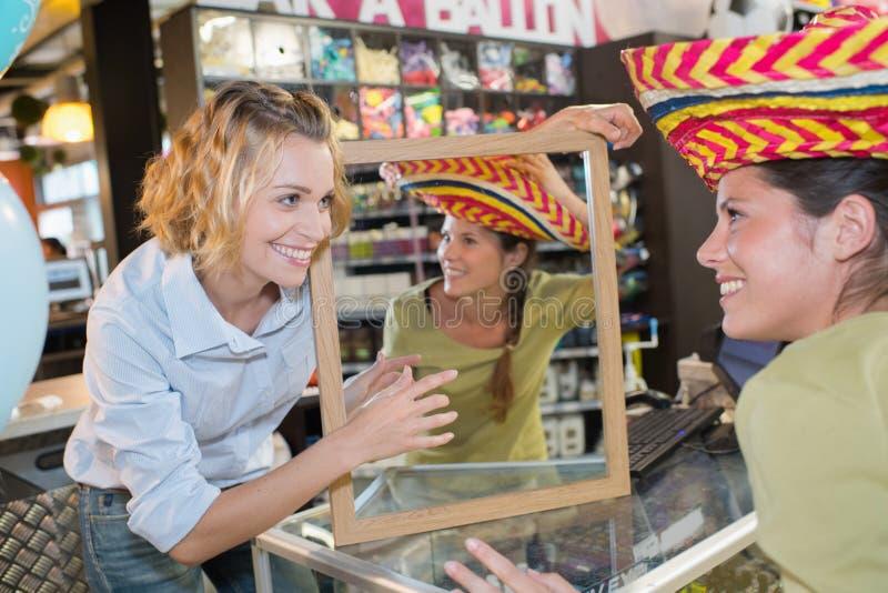 Due giovani amici femminili che provano i cappelli e che fanno divertimento immagini stock libere da diritti