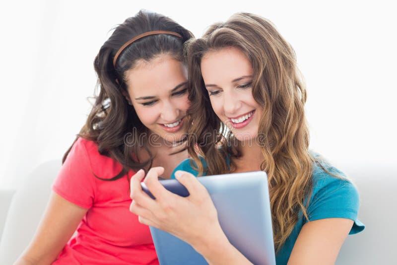 Due giovani amici femminili sorridenti che per mezzo della compressa digitale fotografie stock libere da diritti