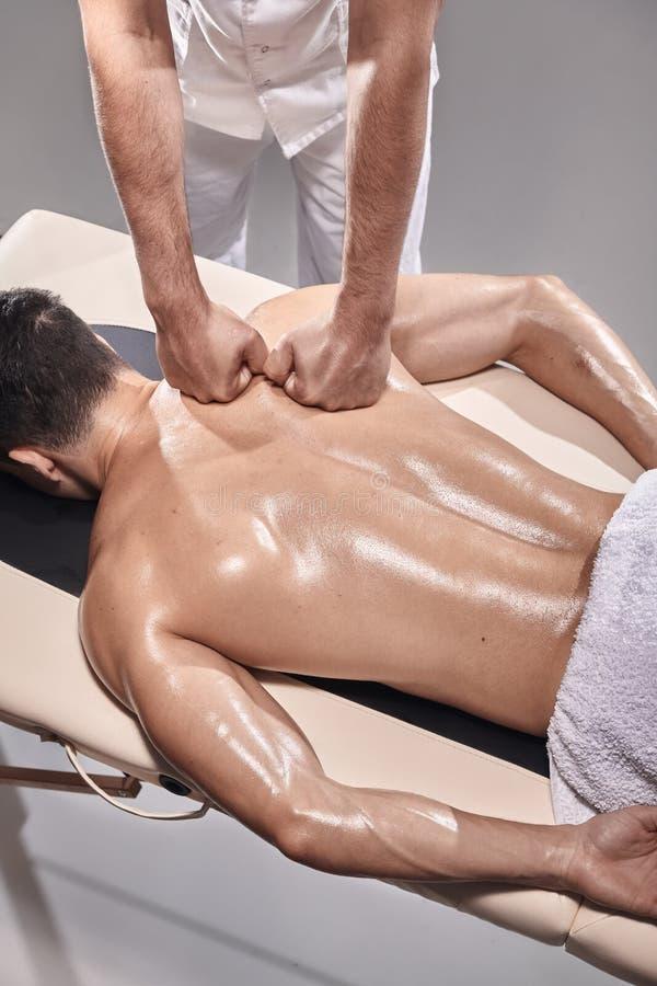Due giovani, 20-29 anni, fisioterapia di sport all'interno in studio, tiro di foto Fisioterapista che massaggia paziente muscolar fotografie stock
