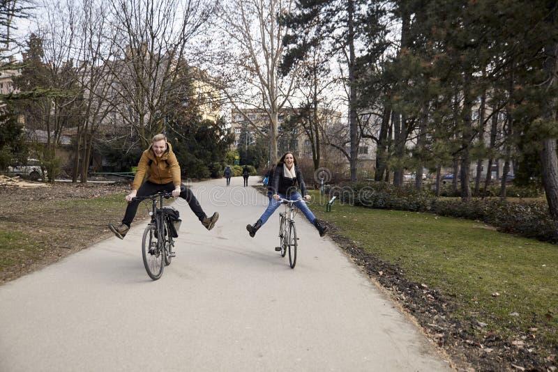 Due giovani, 20-29 anni, guidanti una bicicletta in un parco con le gambe allungate, sciocche, la risata e divertiresi immagine stock