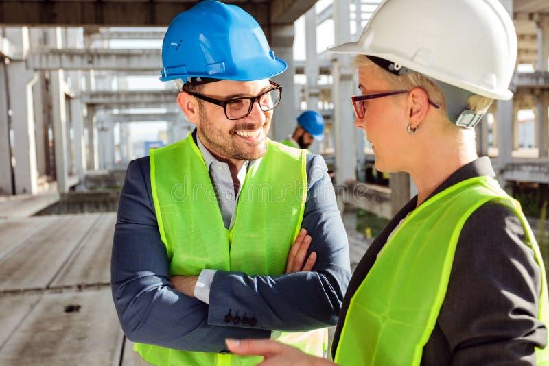 Due giovani architetti o ingegneri civili moderni che parlano dello sviluppo di progetto futuro su un cantiere fotografie stock