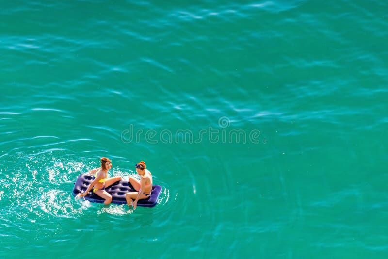 Due giovani belle donne caucasiche in bikini che prendono il sole, spruzzanti e rilassantesi sul materasso su acqua azzurrata cal fotografia stock