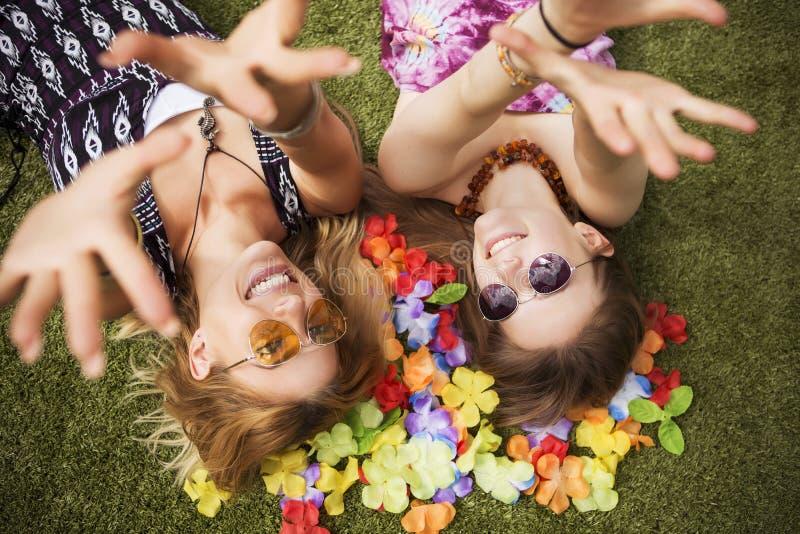 Due giovani belle ragazze bionde dei pantaloni a vita bassa il giorno di estate che ha fu immagine stock libera da diritti
