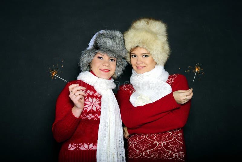 Due giovani belle ragazze con i regali su un fondo bianco fotografie stock libere da diritti