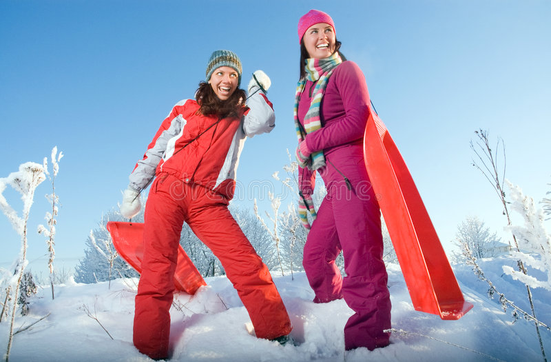 Due giovani belle ragazze con le slitte immagini stock libere da diritti