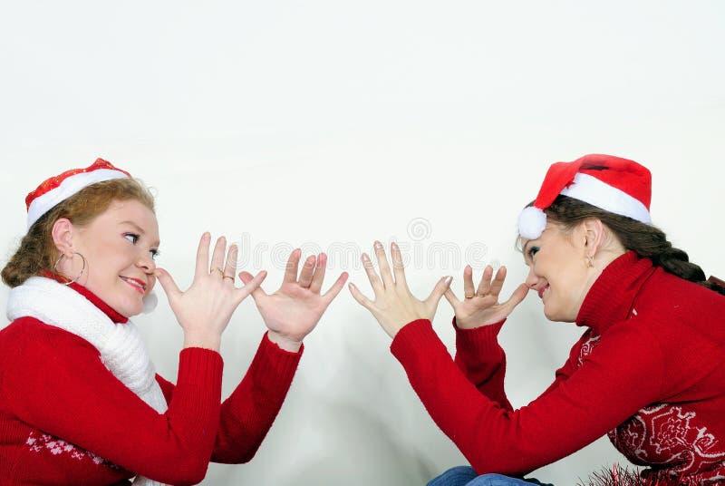Due giovani belle ragazze giocano un fondo bianco immagini stock