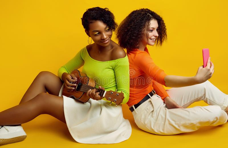 Due giovani belle ragazze hipster in abiti estivi colorati con una chitarra fotografia stock libera da diritti