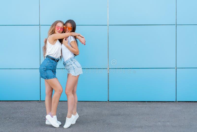Due giovani belle ragazze sorridenti dei pantaloni a vita bassa in occhiali da sole al neon variopinti di estate d'avanguardia Do immagine stock
