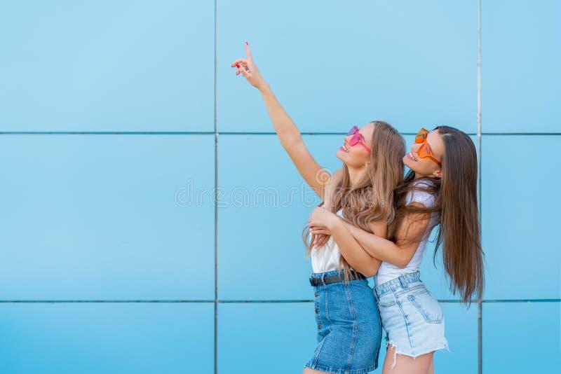 Due giovani belle ragazze sorridenti dei pantaloni a vita bassa in occhiali da sole al neon variopinti di estate d'avanguardia Do fotografia stock libera da diritti