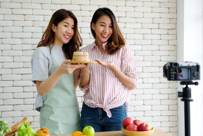 Due giovani blogger asiatici dell'alimento della donna che parlano mentre registrando vide fotografia stock libera da diritti