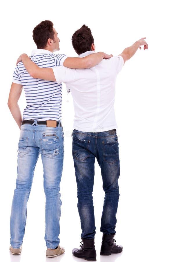 Due giovani che indicano al somethin immagine stock libera da diritti