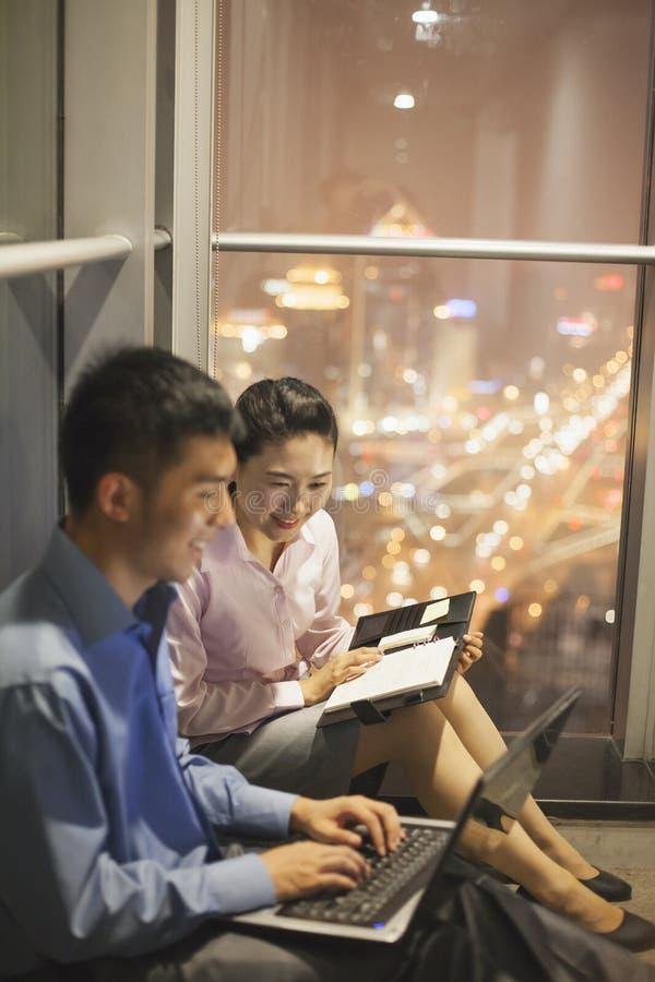 Due giovani che sorridono insieme e che lavorano nell'ufficio alla notte immagini stock